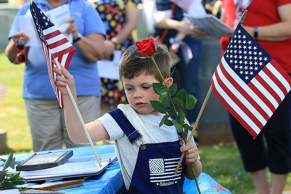 """Corbin Amburgey hands out roses and flags at a ceremony honoring the """"Bedford Boys"""" on Memorial Day in Bedford, Virginia. The small town of Bedford lost 22 soldiers in the Normandy invasion of France on June 6, 1944, in World War II, proportionally the nation's severest D-Day losses. (Jenny Harnish/The Register-Herald)"""