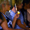 (Brad Davis/The Register-Herald) Attendees look on with electric candles flags in hand during the vigil portion of the 13th annual 9/11 Memorial Service at the Lewis Christian Community Center Wednesday night in Oak Hill.