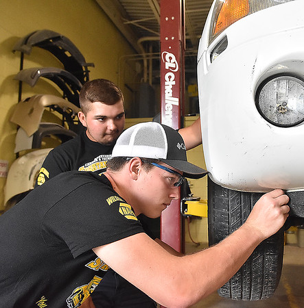 (Brad Davis/The Register-Herald) Greenbrier East juniors Austin Boone, near, and Tyler Boggs work on a vehicle inside the school's collision repair training center May 30 in Fairlea.