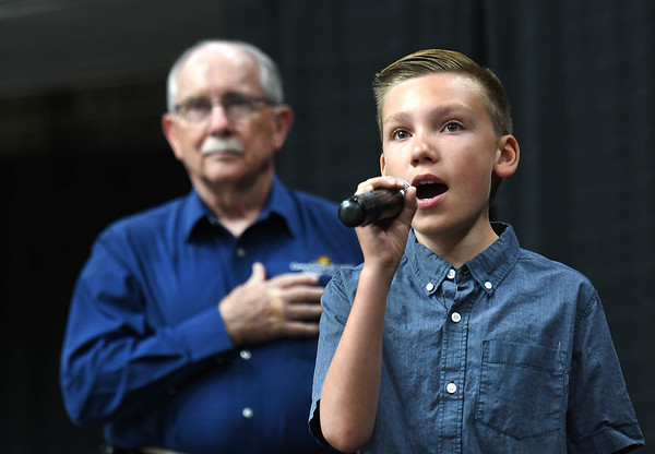 """Max Phillips, 11, of Daniels, sings the National Anthem and listening in background, Jack Tanner, executive director Raleigh County Commission on Aging during """"Senior Day Out"""" held at Beckley-Raleigh County Convention Center. The event had, music bingo, vendors, door prizes, information about products and services for our senior community and was co-sponsored by, The Register-Herald and Raleigh County Commission on Aging.<br /> (Rick Barbero/The Register-Herald)"""