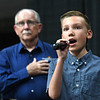 "Max Phillips, 11, of Daniels, sings the National Anthem and listening in background, Jack Tanner, executive director Raleigh County Commission on Aging during ""Senior Day Out"" held at Beckley-Raleigh County Convention Center. The event had, music bingo, vendors, door prizes, information about products and services for our senior community and was co-sponsored by, The Register-Herald and Raleigh County Commission on Aging.<br /> (Rick Barbero/The Register-Herald)"