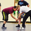 Greenbrier West wrestling coach Jeremy Tincher demonstrates a move with Brad Blevins during their practice at the school in Charmco on Tuesday. (Chris Jackson/The Register-Herald)