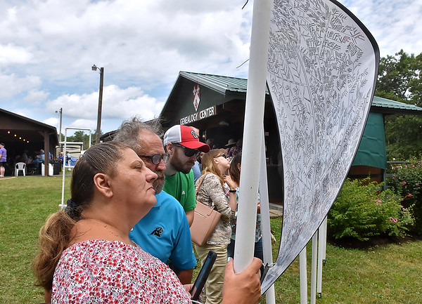 (Brad Davis/The Register-Herald) Telena Lucas, left, Freddie Lucas (blue shirt) and others try to track down their place in history on one of several, ever-growing family trees printed and on display at the Lilly Reunion Saturday.