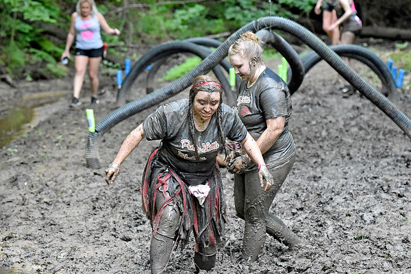 (Brad Davis/The Register-Herald) Participants trudge through quicksand-like mud as they and hundreds of others tackle the courses at the Gitty Chix Mud Run Saturday morning at ACE Adventure Resort.