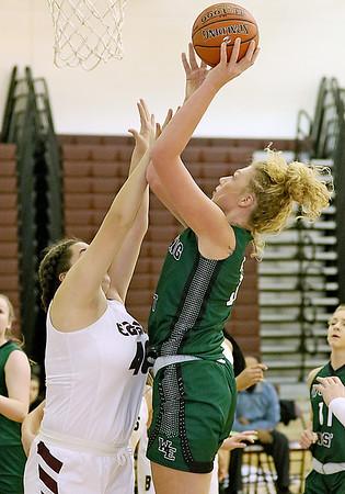(Brad Davis/The Register-Herald) Wyoming East's Emily Saunders scores as Woodrow Wilson's Caroline Felton defends Saturday night in Beckley.