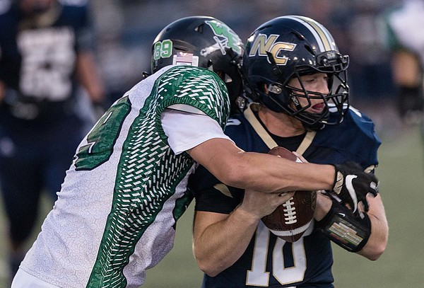 Nicholas County quarterback, , is wrapped up in the backfield by Wyoming East Warrior, Jacob Bishop. Chad Foreman for the Register-Herald.
