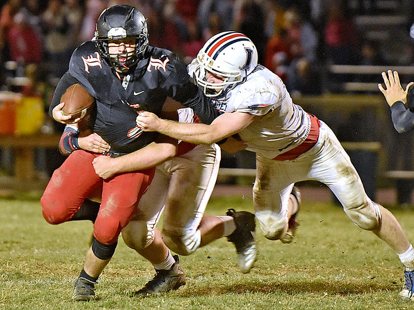 (Brad Davis/The Register-Herald) Liberty quarterback Issac Atkins is flushed from the pocket and tackled by Independence defenders Jacob Hatcher, right, and Hayden Miller Friday night in Glen Daniel.