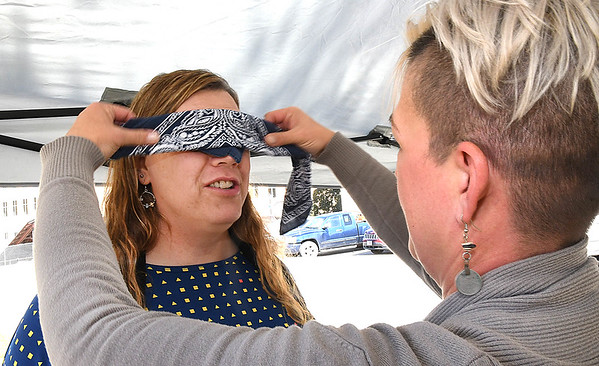 Kelly Elkins, cummunity resources facilitator Mountain State Centers for Independent Living, right, blindfolds Danielle Stewart during the White Cane Safety Day held in Word Park in Beckley Tuesday afternoon. There were vendors, obstacle course for sighted people to get an idea of what it might be like to be blind. They also provided federation for Blind brochures, some in braille, including the alphabet so you can learn the braille alphabet and learn more about the services provide to the community.<br /> (Rick Barbero/The Register-Herald)