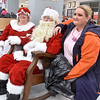 (Brad Davis/The Register-Herald) Shopper Angie Perry, right, shows that you're never too old to have your picture taken with Santa and Mrs. Claus during the Wyoming County Toy Fund event Sunday morning at Wyoming East High School.