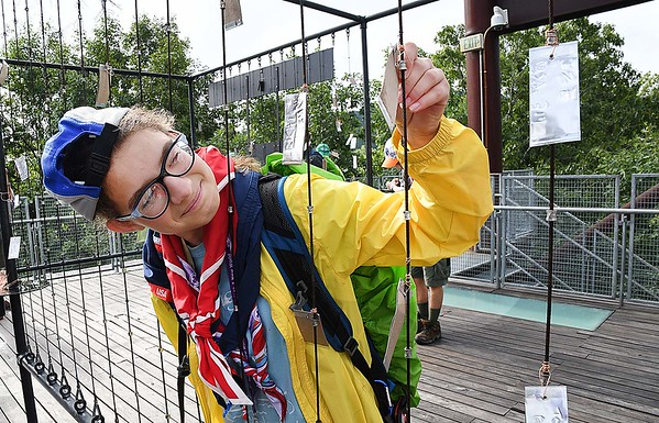 Kathleen Strous, of Columbus, OH, places a pledge on a cable on top of the Sustainability Treehouse, to live a more earth friendy life, during the World Scout Jamboree at the Summit Bechtel Reserve in Glen Jean.