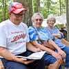 (Brad Davis/The Register-Herald) Elliston, Virginia resident Daniel Lilly, left, browses the 90th Anniversary reunion program and yearbook with wife JoAnn, middle, and sister Annie Lilly Geiger during the Lilly Family Reunion Saturday afternoon in Flat Top.