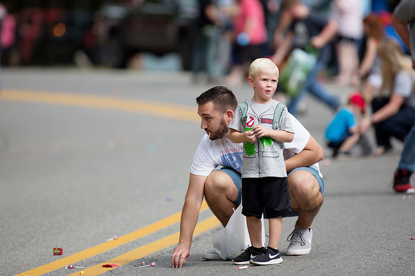 Josh Thompson, from Sausville, helps his step-son Case Ashley, 4, get candy during the Labor Day Parade in Pineville on Monday. (Chris Jackson/The Register-Herald)