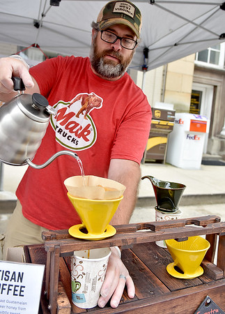 (Brad Davis/The Register-Herald) Jason Young, co-owner of the White Oak Bee Company makes coffee samples featuring beans roasted with their honey during the Appalachian Fest Block Party August 24 in Beckley.