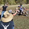 (Brad Davis/The Register-Herald) A rider grabs a bottle of sports drink from supporting fans and family as he competes in the Amsoil Grand National Cross Country Racing Series event Sunday afternoon at the Summit Bechtel Reserve.