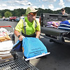 (Brad Davis/The Register-Herald) Rural King employee Andrew Fleshman performs his duties as a loader, lugging heavy bags of bird seed, mulch and other items into customer Dewayne Varney's truck as he looks on Sunday afternoon.