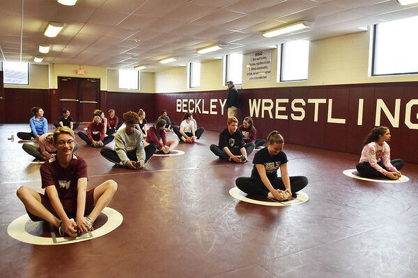 Woodrow Wilson coach Bernie Bostick monitors his team during fitness training on a rainy day of practice in Beckley on Thursday. (Chris Jackson/The Register-Herald)