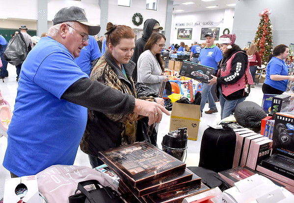 (Brad Davis/The Register-Herald) Volunteer Wink Houck, left, guides shopper Crystal Stewart as she picks out gifts during the Wyoming County Toy Fund event Sunday morning at Wyoming East High School.