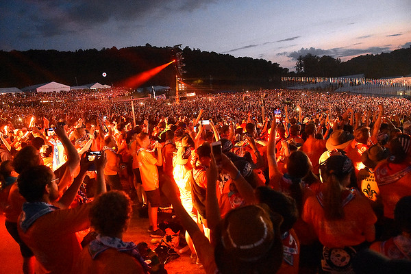 (Brad Davis/The Register-Herald) The orange beacons of every scout on site comes to life as the World Scout Jamboree's Cultural Celebration commences Friday night at the Bechtel Summit Reserve.