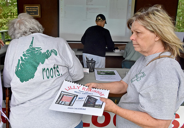 (Brad Davis/The Register-Herald) Carol Meadows, right, picks up a Lilly Reunion calendar as Myra Taylor, left, sifts through records and photos of relatives past and present at the Geneology Center, a major hive of activity during the 90th annual Lilly Family Reunion Saturday afternoon in Flat Top. Meadows and Taylor, who each had Lilly grandparents, had matching Marshall University shirts on for the occasion.