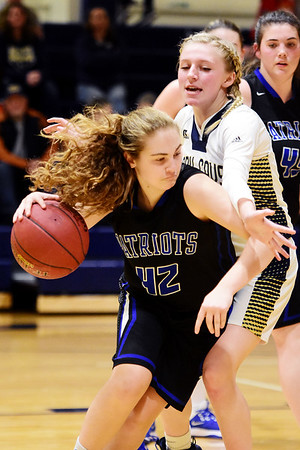 Midland Trail's Emily Dickerson (42) grabs a rebound over Greenbrier West's Brooklyn Morgan (22) during the first of their basketball game in Charmco on Thursday. (Chris Jackson/The Register-Herald)
