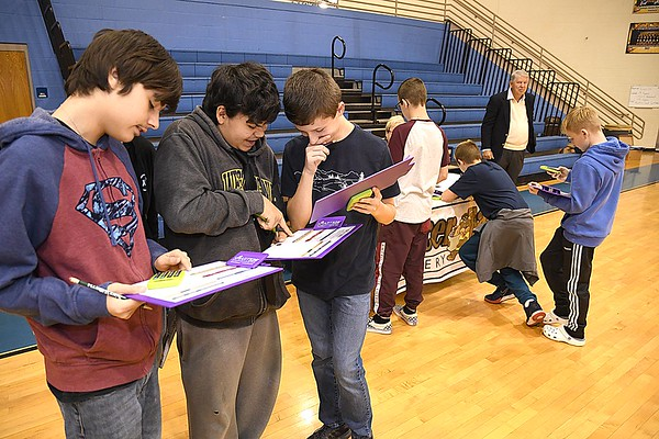 "Nikolas Kesler, left, Lorenzo Enriquez and Payton Stover students at Shady Spring Middle School, checking out their finances before making a purchase of a car and house during the, ""Get a Life"" program sponored by the State Treasurer's office and Raleigh County Chamber of Commerce. The program teaches students how to better prepare themselves with finances after graduating from school.<br /> (Rick Barbero/The Register-Herald)"
