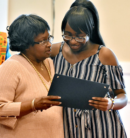 (Brad Davis/The Register-Herald) High School Graduate Hannah King, right, comes forward as one of 19 seniors recognized for academic excellence during the annual BEAUTY Graduate Celebration and Awards Ceremony Saturday afternoon at Central Baptist Church. Of those 19 students recognized, 10 received $1,000 scholarships towards their upcoming college careers. Now in its second year, BEAUTY (Black Educators Are United Totally - Yes!) is continuing in its mission to encourage, mentor, uplift, motivate and inspire African American youths to reach their fullest potential. They are comprised of retired and active black educators an counselors devoted to providing equal scholarly opportunities for those who might not have the same access.