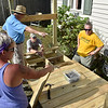 (Brad Davis/The Register-Herald) From left, volunteers Kelly Elkins, Parr Claytor, Chuck Noll and Debbie Moreland, labor through the hot Sunday sun as they plot their next steps in contructing a wheelchair ramp for Harper Heights resident Debbie Green, who's had to be lifted or carried up her stairs by accompanying family for the last four years.