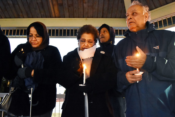 Amna Zahir, center, from Beckley, holds a candle as Najma Faheem, left, and Dr. Syed Zahir, right, do the same during a candlelight vigil to honor those killed in Christchurch massacre in New Zealand last week at Word Park in Beckley on Thursday. Around 50 people attended the vent, hosted by the Beckley Human Rights Commission. (Chris Jackson/The Register-Herald)