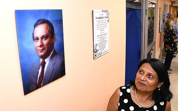 Hina Shah, wife of the late Dr. R.C. Shah, MD, view a picture and a poem displayed on the second floor after unveiling the R.C. Shah, MD Sugical Center sign on the wall at Beckley ARH Hospital.<br /> (Rick Barbero/The Register-Herald)