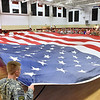 (Brad Davis/The Register-Herald) The crowd watches as members of the Oak Hill High School Jr. R.O.T.C. program unfurl a huge American flag during the opening moments of the 13th annual 9/11 Memorial Service at the Lewis Christian Community Center Wednesday night in Oak Hill.
