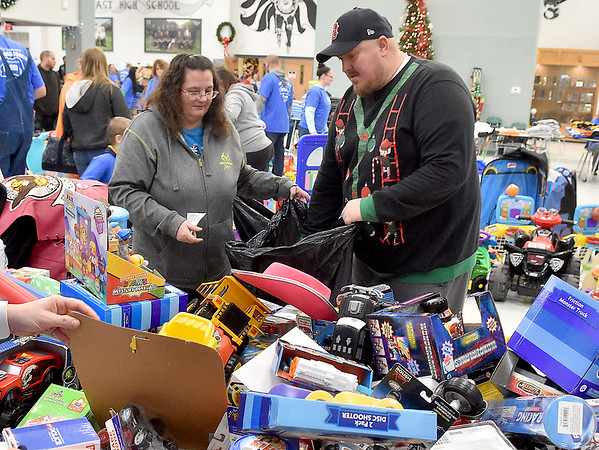 (Brad Davis/The Register-Herald) Christmas sweater-clad volunteer Nathan England helps shopper Sherry Morgan find the right gifts during the Wyoming County Toy Fund event Sunday morning at Wyoming East High School.