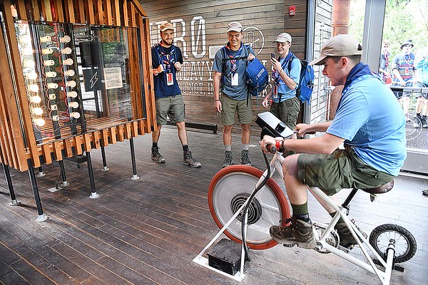 Thomas Franks, left, Alex Li and Michael Shetron, watch John Sheron, all scouts from Batesville, AK, peddle the bike at the Recyclotron station in the Sustainability Treehousethat demonstrates on how to save energy during the World Scout Jamboree at the Summit Bechtel Reserve in Glen Jean.