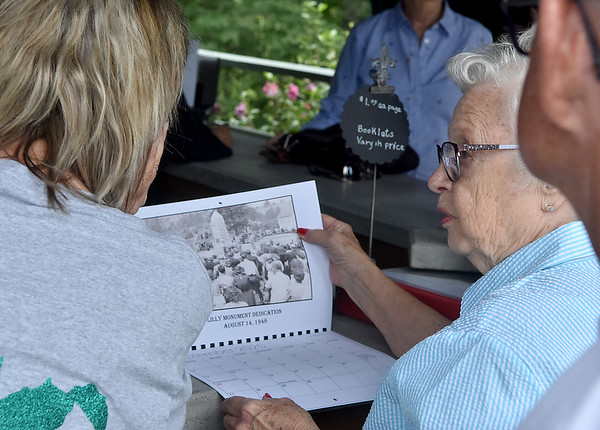 (Brad Davis/The Register-Herald) Abbington, Virginia resident Jane Martin, right, adds some insight to historic photos with Carol Meadows, left, as a crowd buzzes around the geneology center during the 90th annual Lilly Family Reunion Saturday afternoon in Flat Top.