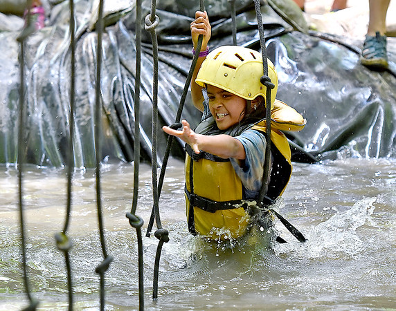 (Brad Davis/The Register-Herald) Indiana Girl Scout Raksha Suresh (Troop 00377 in Middlebury) swing from one rope to the other as she tackles the tarzan ropes along the mud obstacle course during the Girls Scouts' Girl Fest event Friday afternoon at ACE Adventure Resort. Hosted by the Girl Scouts of Black Diamond Council, over 216 scouts from 22 different states camped out at ACE through the week, taking part in outdoor activities from rock climbing and hiking to whitewater rafting and zip lining, along with several educational programs by the National Park Service, U.S. Department of Agriculture and others.