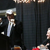 "Charlie Houck speaks while wearing a hat that reads ""Make West Virginia Basketball Great Again"" as West Virginia University Men's Basketball Head Coach Bob Huggins laughs during the 32nd Annual Spirit of Beckley Awards Presentation at the Beckley-Raleigh County Convention Center in Beckley on Monday. (Chris Jackson/The Register-Herald)"