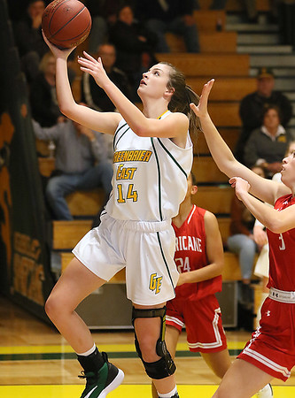(Brad Davis/The Register-Herald) Greenbrier East's Taylor Dunbar drives and scores as Hurricane's Nadia Legros defends Saturday night in Fairlea.