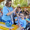 (Brad Davis/The Register-Herald) Contestant Maverick Davis, 6, gets a high five from Ms. Beckley Kids Classic Macalah Lefler after the excited youngster's hamster won a race during the Kids Classic Hamster Races Sunday afternoon at the Youth Museum.