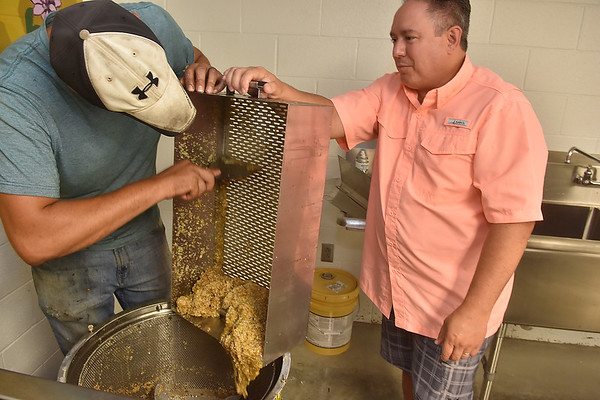 (Brad Davis/The Register-Herald) Beekeeper Sean Phelps, left, scrapes wax from the extracted trays into a wax spinner which will separate the wax and leftover honey. Darrin Butcher, Treasurer of Ral Co Board of Ed and himself a home beekeeper at right.