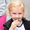 (Brad Davis/The Register-Herald) Three-year-old Paisleigh Johnson nibbles on a bite size Chocolate Caramel Mocha cupcake from the White Oak Bee Company during the Appalachian Fest Block Party August 24 in Beckley.