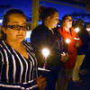 (Brad Davis/The Register-Herald) From left, Rebecca Hudson, Kaitlyn Gunno and Rebecca Stover join other attendees in observing a moment of silence for victims lost to domestic violence as their candles burn bright during the closing moments of the Women's Resource Center's 29th Annual Candlelight Vigil Thursday night under the Jim Word Memorial Park gazebo.
