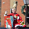 (Brad Davis/The Register-Herald) A young parade participant sports the Grinch hairstyle as she tosses candy to the masses during the Beckley Christmas Parade Saturday morning.
