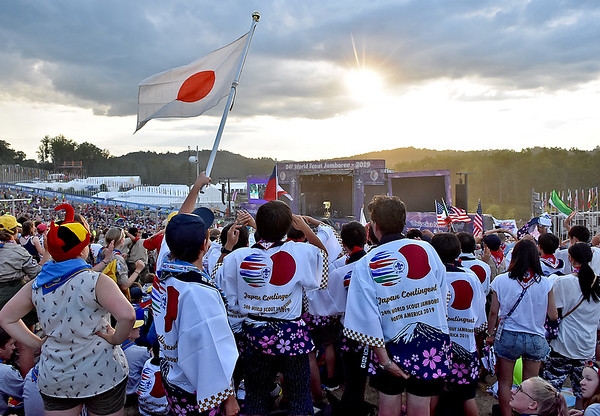 (Brad Davis/The Register-Herald) Japanese scouts wave their flag as festivities get underway at the World Scout Jamboree's Cultural Celebration Friday night at the Bechtel Summit Reserve.