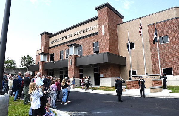 Beckley police officeres raise the flags during the ribbon cutting dedication ceremony held at the new Beckley Police Department headquarters on 501 Neville Street.<br /> (Rick Barbero/The Register-Herald)