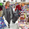 (Brad Davis/The Register-Herald) Shoppers Robin Hatfield, left, and Elizabeth Sherfey, middle, fill their bags full of Christmas goodies during the Wyoming County Toy Fund event Sunday morning at Wyoming East High School.