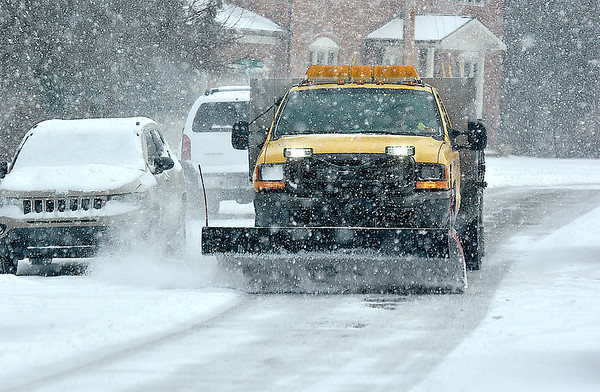 (Brad Davis/The Register-Herald) A city plow truck works around parked vehicles along Woodlawn Avenue while keeping the streets clear in the midst of a burst of snow showers Sunday afternoon in Beckley.