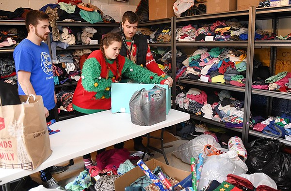Robert Coleman, student president, left, Jullian Mitchell, vice president and Logan Severt, junior, sort through donated clothes for their Christmas Market that will take place in the Shady Spring High School cafetera, Friday, December, 20 from 3 p.m. to 6 p.m.