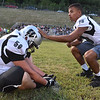 (Brad Davis/The Register-Herald) Jace Colucci, right, pats teammate Logan Shumate on the helmet as he encourages his fellow Renegades through warm-ups before the kickoff at in-county rival Wyoming East Friday night in New Richmond.