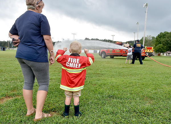 (Brad Davis/The Register-Herald) Young firefighting fan Adam O'Dell, 3, gets a huge kick out of watching fellow kids get the chance to use a real fire hose before getting his own turn as mom Anna O'Dell looks on during a special Public Safety Day event at Veterans Memorial Park in Summersville Friday afternoon. The event was tied into the final day of the season of Summersville's Popsicles in the Park, which happens every 2nd Friday of the month from May to August and will again next year. Area fire departments were on hand to show off their gear and put on vehicle extraction demos, while area police performed K-9 search demos. Veterans Memorial Park will continue to buzz with activites going forward, with Yoga in the Park every Tuesday year-round from 6:00-7:00 p.m., and a community yard sale set for October 5.