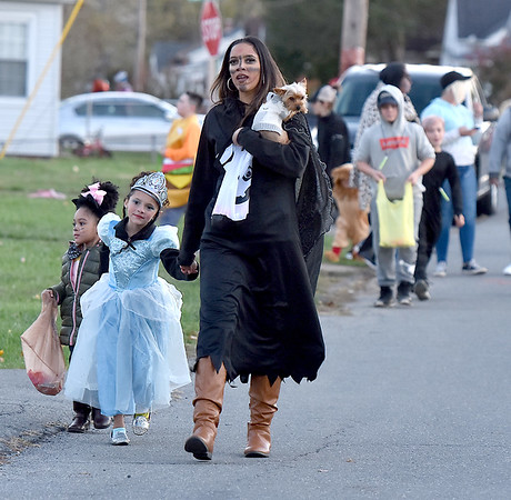 (Brad Davis/The Register-Herald) Domanick Thompson, carrying her dog Chloe, leads her young trick or treaters Malayla, middle, and Hazel, far left, as they join other residents along Orchard Avenue Saturday evening in Beckley.
