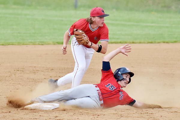 Oak Hill's Lane Jordan (8) and Independence's David Wilson (15) look to the umpire for the call on a tag that Jordan made on Wilson during their Class AA Region 3, Section 1 tournament game in Oak Hill on Thursday. Wilson was tagged out. (Chris Jackson/The Register-Herald)